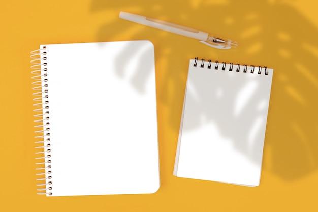 Bloco de notas da vista superior em fundo amarelo, maquete, criador de cena