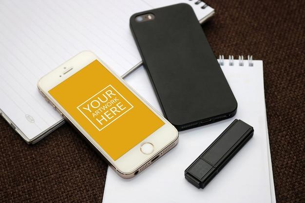 Bloco de notas espiral com smartphone e flash drive