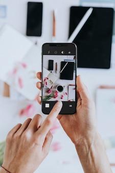 Blogger tirando uma foto com uma maquete de telefone celular