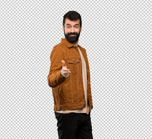 Bonito homem com barba, apertando as mãos para fechar um bom negócio
