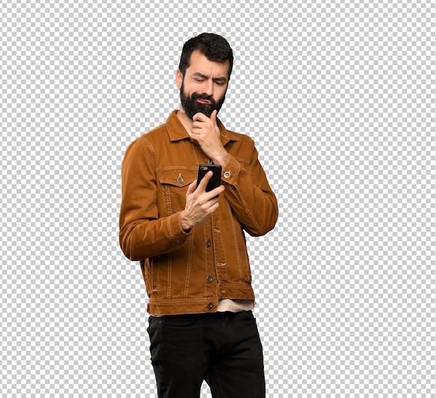 Bonito homem com barba, pensando e enviando uma mensagem