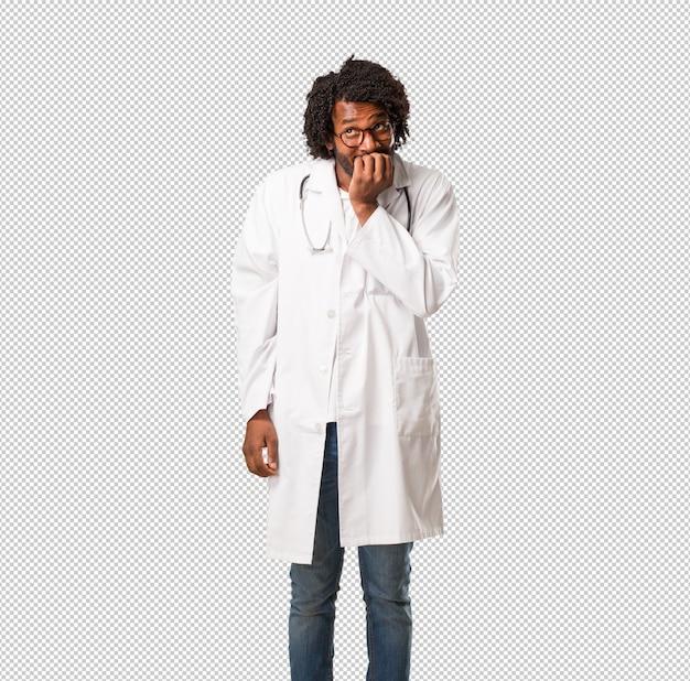 Bonito, médico americano africano, morder, pregos, nervoso, e, muito, ansioso, e, assustado, para, a, futuro, sente, pânico, e, tensão