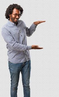 Bonito, negócio, homem americano africano, segurando, algo, com, mãos, mostrando, um, produto, sorrindo, e, alegre, oferecendo, um, imaginário, objeto