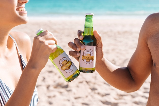 Brindando com duas garrafas de beterraba na praia