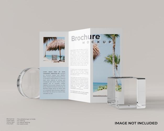 Brochura com três dobras com uma caixa de vidro quadrada e um vidro cilíndrico parece vista frontal