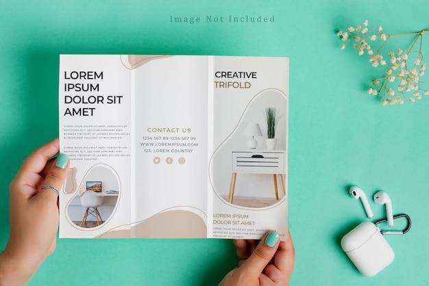 Brochura de trihold papel vazio mock-up para seu projeto nas mãos da mulher