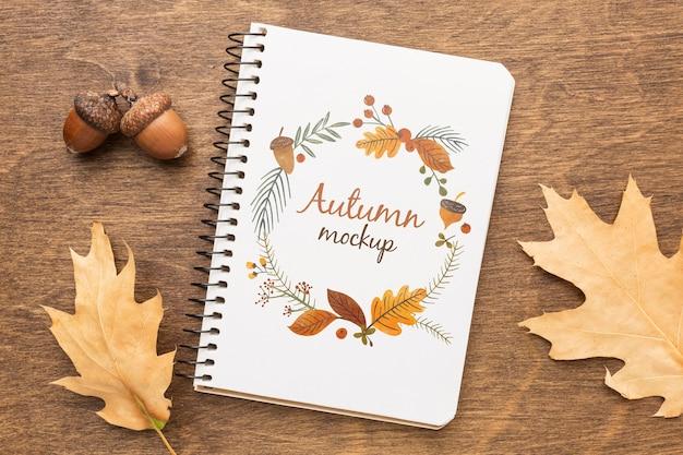 Caderno com bolotas e folhas ao lado