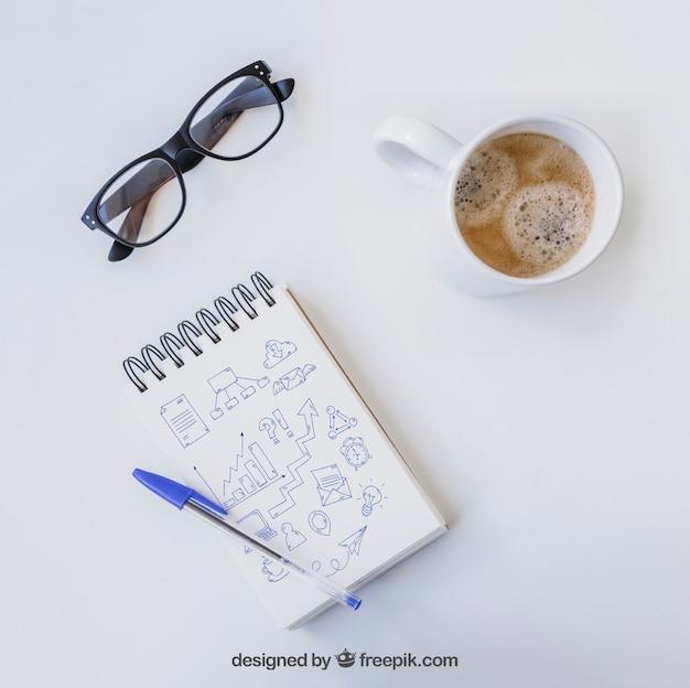Caderno com caneta, óculos e café