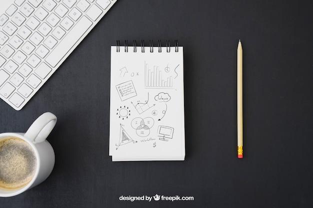 Caderno com desenho a lápis, teclado e caneca de café