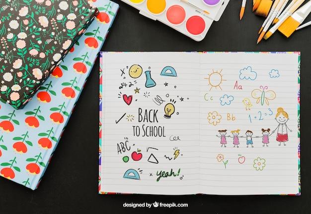 Caderno com desenhos de mão e materiais escolares