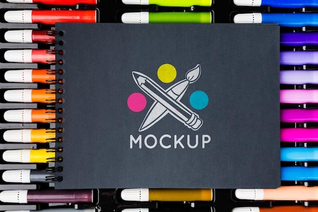 Caderno com vista superior em marcadores coloridos