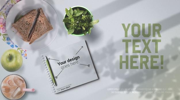 Caderno de maquete de almoço escolar e comida saudável na vista superior de mesa branca