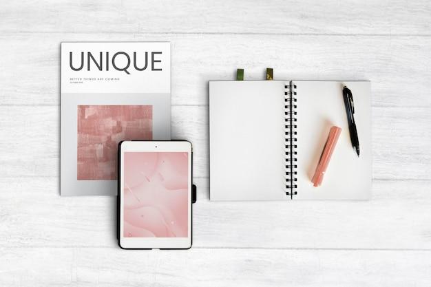 Caderno em branco e um tablet em uma superfície de madeira Psd Premium