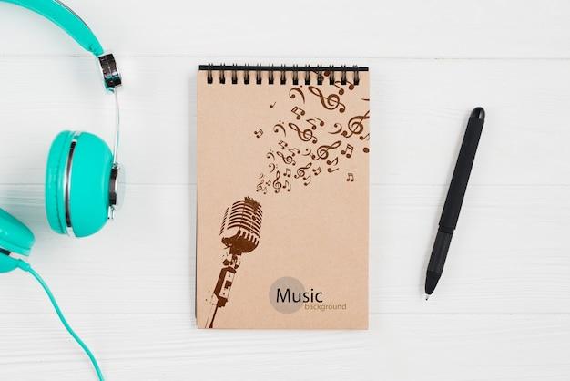 Caderno para notas musicais com fones de ouvido ao lado