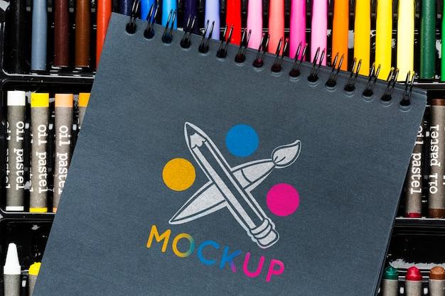Caderno plano sobre marcadores coloridos