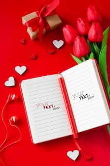 Caderno vermelho com buquê de tulipas, caixa de presente, corações de madeira, lápis e fones de ouvido.