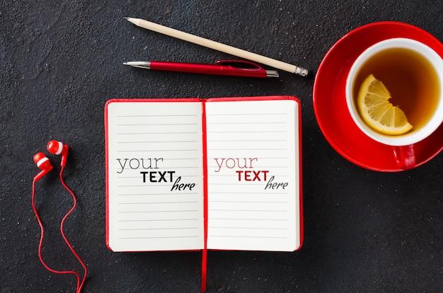 Caderno vermelho em branco, computador portátil, fones de ouvido e xícara de chá. conceito de negócios ou educação.