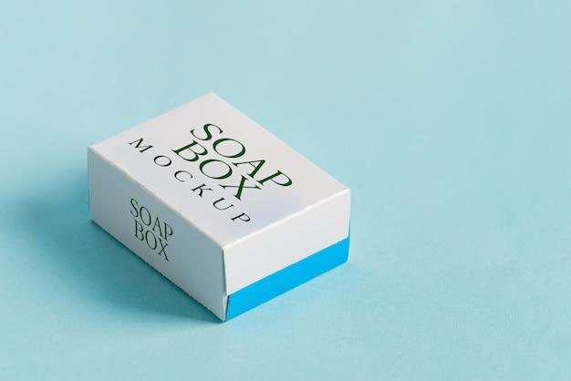 Caixa de papel mock-se artesanal para produtos e mercadorias de pacote sobre um fundo azul claro com sombras suaves.