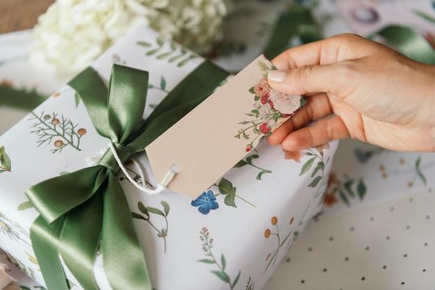 Caixa de presente embrulhada em papel estampado floral com maquete de cartão