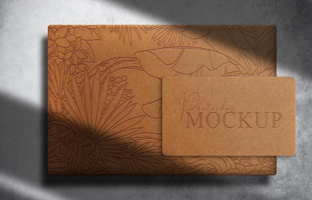 Caixa em relevo de papel marrom de luxo e maquete de cartão de visita