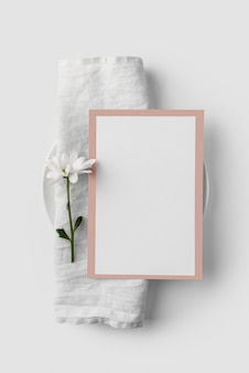 Camada plana da disposição da mesa com modelo do menu de primavera na toalha e na flor