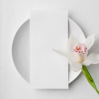 Camada plana da maquete do menu de primavera no prato com flor