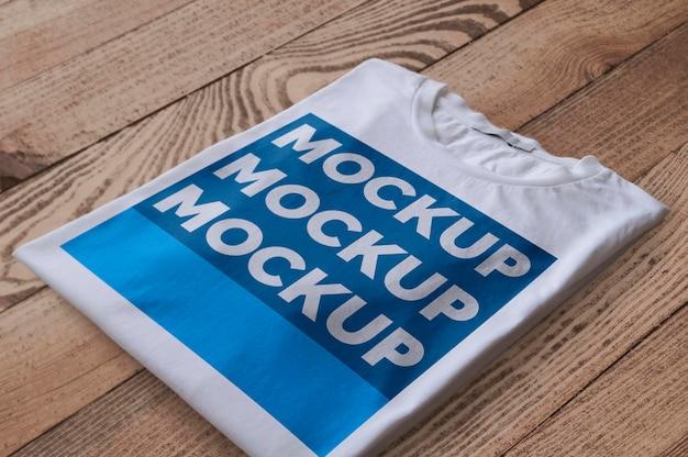 Camiseta branca dobrada sobre maquete de superfície de madeira