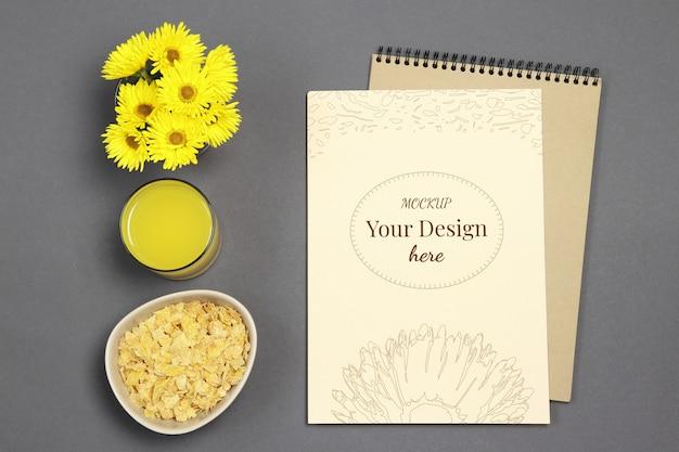 Carta de maquete sobre fundo cinza com flores amarelas, suco fresco e flocos