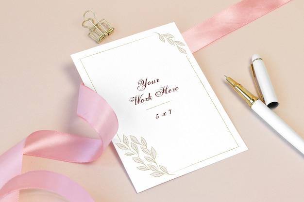 Cartão de convite de maquete com fita rosa e caneta
