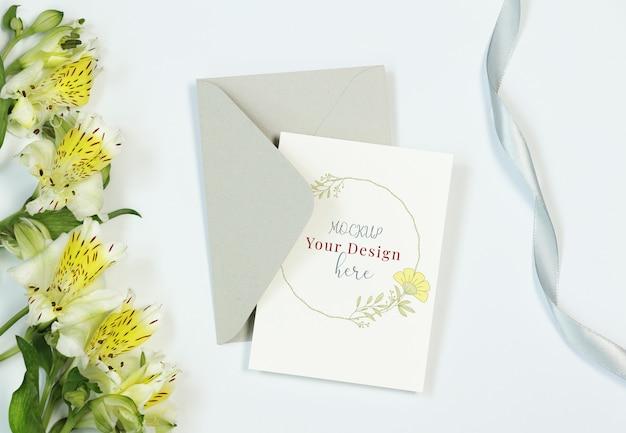 Cartão de convite de maquete sobre fundo branco com flores, envelope e fita