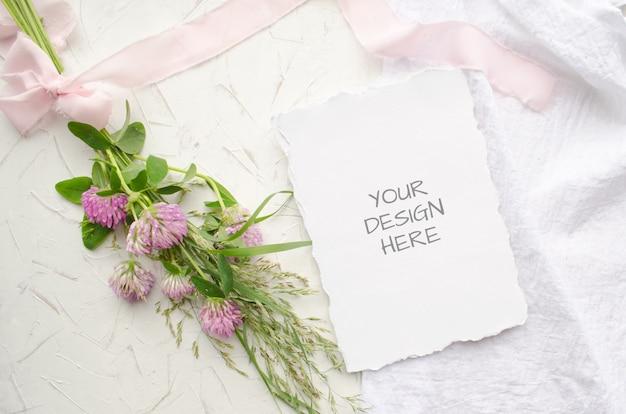 Cartão de maquete de casamento com flores cor de rosa e delicadas fitas de seda em branco