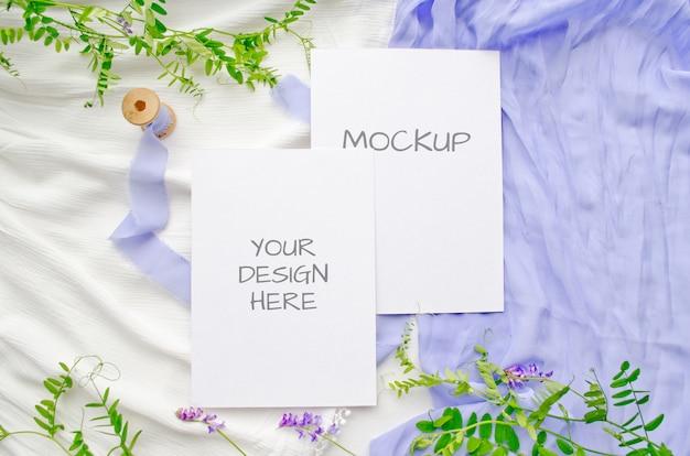 Cartão de maquete de papelaria verão ou convite de casamento com flores violetas e delicadas fitas de seda em branco