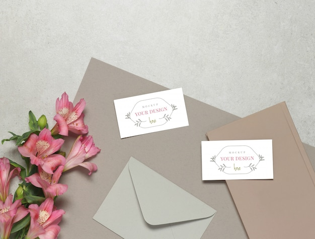 Cartão de negócios de maquete sobre fundo cinza, flores frescas, envelope cinza e notas-de-rosa