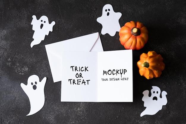 Cartão de papel em branco com fantasmas bonitos em fundo escuro de concreto. modelo para o feriado do dia das bruxas