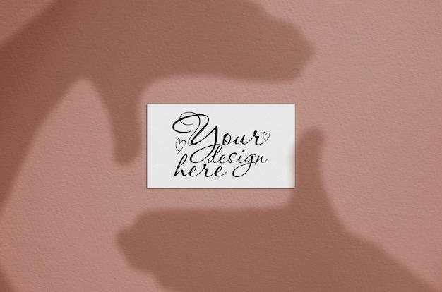 Cartão de visita em branco branco com sobreposição de sombra do quadro na mão. cartão de marca moderna e elegante mock up