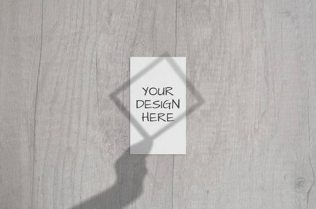 Cartão de visita vertical branco em branco com sobreposição de sombra do quadro na mão. cartão de marca moderna e elegante mock up