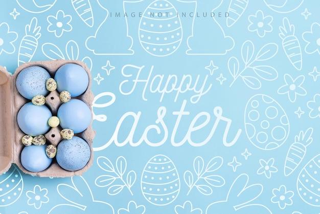 Cartão postal de maquete com recipiente de papel artesanal pintado de ovos azuis em uma superfície de cor azul, feliz páscoa