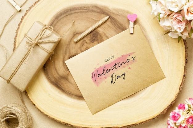 Cartão postal de maquete e envelope na madeira para dia dos namorados