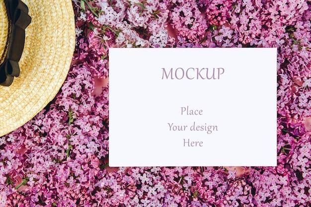 Cartão postal de maquete em um fundo de galhos lilás e um chapéu de palha