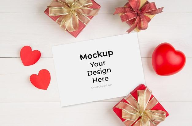 Cartão postal em branco, caixa de presente e formato de coração na mesa de madeira