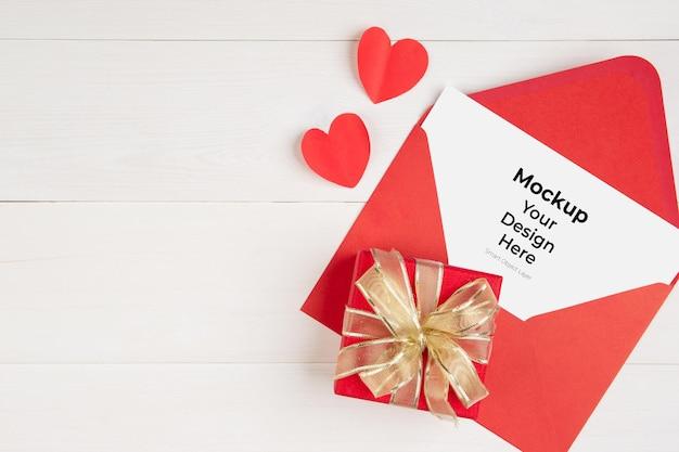 Cartão postal em branco e carta e caixa de presente e formato de coração na mesa de madeira