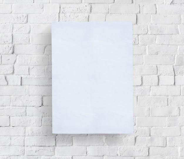 Cartaz em branco na frente da parede de tijolo