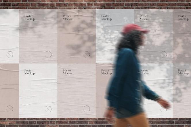 Cartazes colados em maquete de parede de tijolos