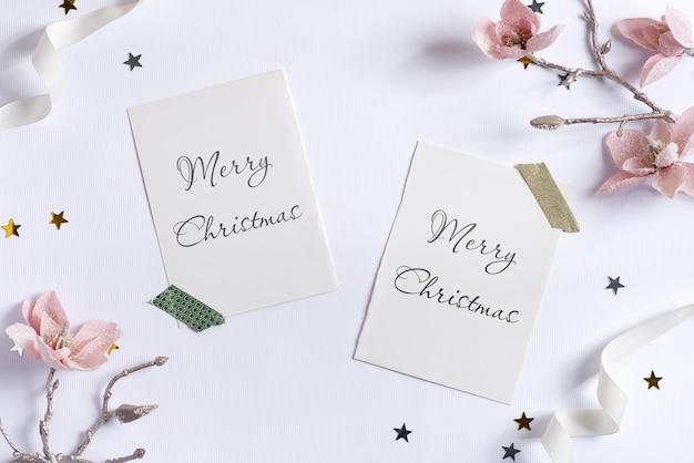 Cartões de maquete de feliz natal e flores artificiais.