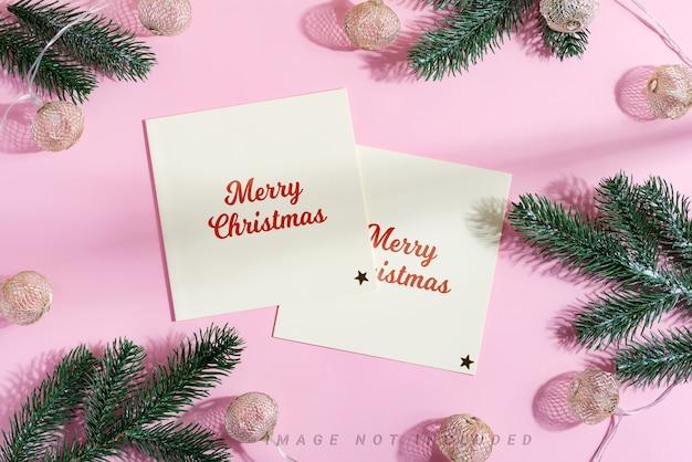 Cartões de natal de maquete com guirlanda clara e galhos de pinheiro verde