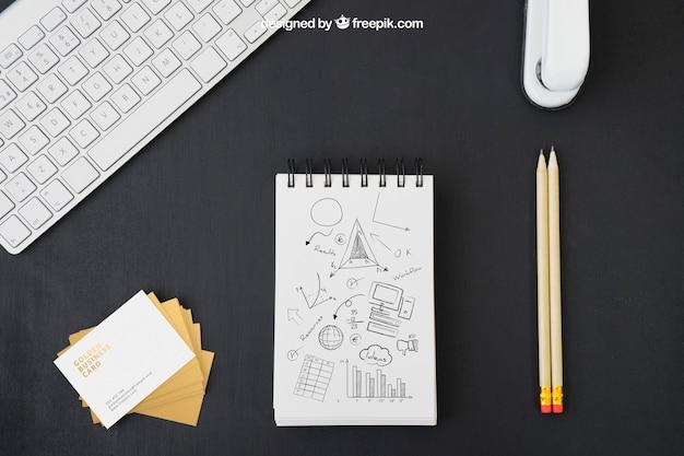 Cartões de visita, mesa de escritório e desenhos a lápis