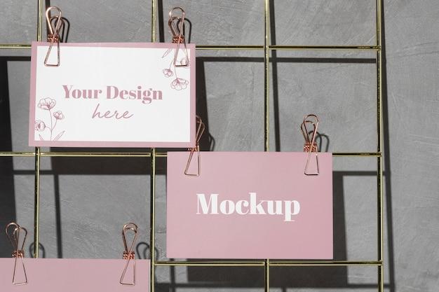 Cartões pendurados na placa de arame com clipes rosa