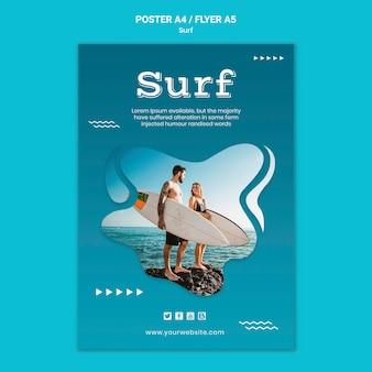 Casal à beira-mar com pôster de pranchas de surf