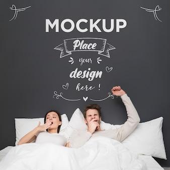 Casal cansado em maquete de cama