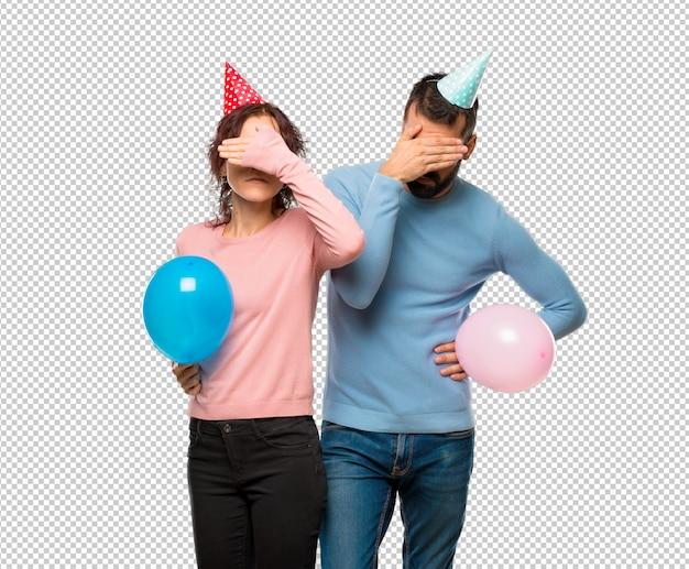 Casal com balões e chapéus de aniversário cobrindo os olhos pelas mãos. não quero ver algo
